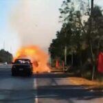 Muž přes město veze hořící náklad na vozíku